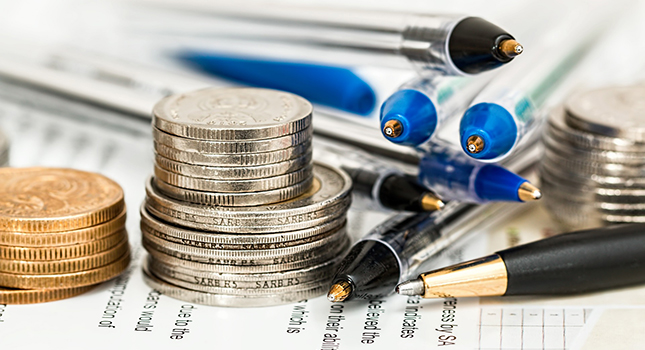 Bilden visar pengar, pennor och kalkylpapper.