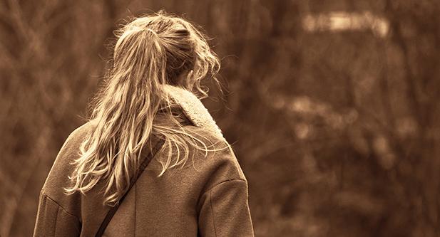 Flicka som går i en skog